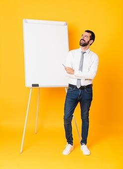 Het schot van gemiddelde lengte van zakenman die een presentatie op wit bord over geïsoleerde gele gelukkig en achtergrond geven die glimlachen