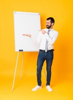 Het schot van gemiddelde lengte van zakenman die een presentatie op wit bord over geïsoleerde gele holding copyspace denkbeeldig op de palm geven om een advertentie op te nemen