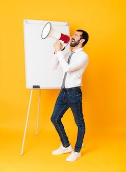 Het schot van gemiddelde lengte van zakenman die een presentatie op wit bord over het geïsoleerde gele schreeuwen door een megafoon geven