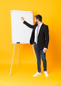 Het schot van gemiddelde lengte van zakenman die een presentatie op witte raad over geïsoleerde geel geeft