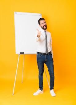 Het schot van gemiddelde lengte van zakenman die een presentatie op witte raad over geïsoleerde geel met omhoog duimen geeft