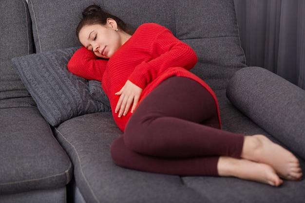 Het schot van rustgevende zwangere vrouw houdt hand op buik, draagt vrijetijdskleding, ligt op comfortabele bank, gaat dutje doen