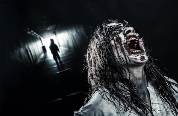 Het schreeuwende horrorzombiemeisje in een donkere gang. halloween.