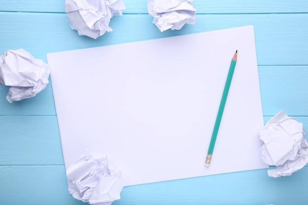 Het schrijven van concept - verfrommelde omhoog document pakjes met een blad van witboek en potlood op blauwe houten