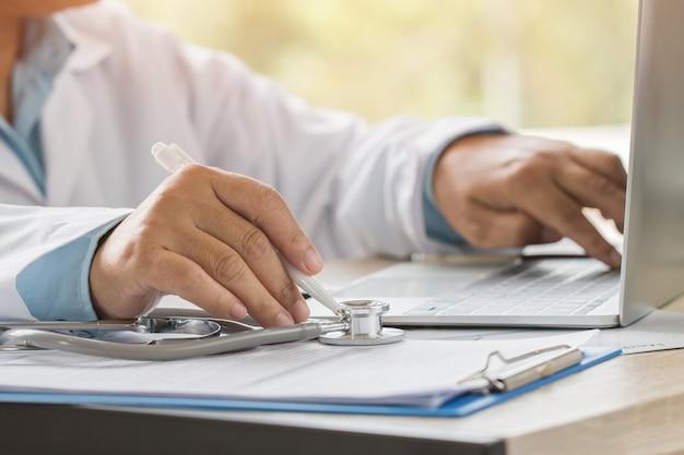 Het schrijven van de arts en het werken aan laptop computer, die voorschriftklembord met verslaginformatie schrijven