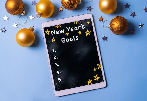 Het schrijven van de doelstellingenlijst voor het nieuwe jaar op een tablet op blauwe achtergrond met gouden kerstballen en zilveren sterren