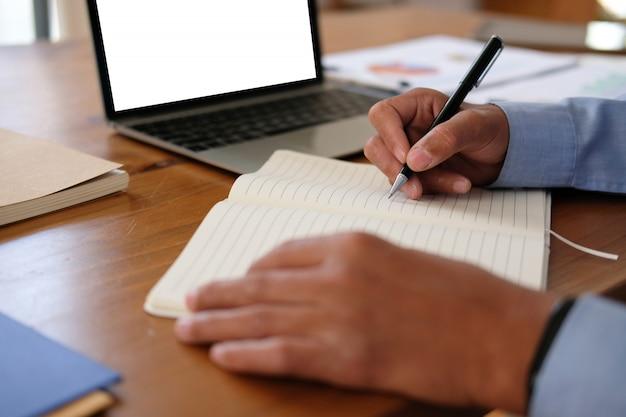 Het schrijven van de mens nota over notitieboekje, zakenman het werken organiserend plan op het werk