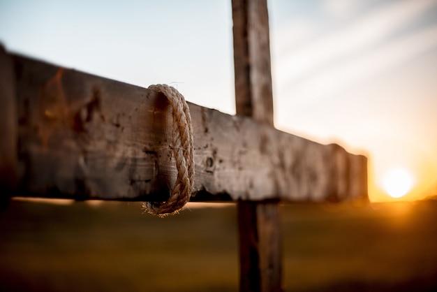 Het selectieve nadrukschot van een hand maakte een houten kruis met rond verpakt kabel en vage achtergrond