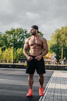 Het sexy fitness sportman stellen op een topless sportterrein. fitness, bodybuilding, gezonde levensstijl