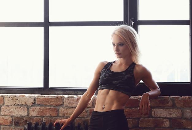 Het sexy gespierde atletenvrouw stellen op venster