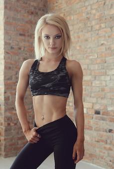 Het sexy gespierde atletenvrouw stellen