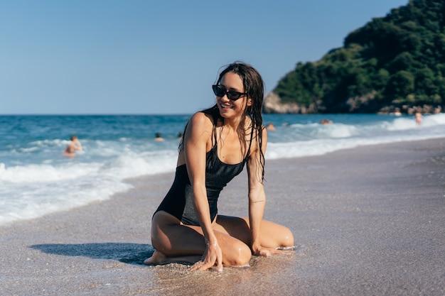 Het sexy jonge donkerbruine stellen op haar knieën in het overzees
