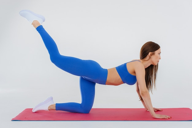 Het sexy jonge meisje voert sportoefeningen op een witte muur uit. fitness, gezonde levensstijl.