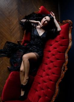 Het sexy langharige donkerbruine kaukasische meisje kijkt recht en ligt op de rode bank gekleed in zwarte kantkleding