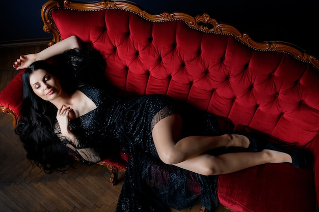 Het sexy langharige donkerbruine kaukasische meisje met gesloten ogen ligt op de luxe rode bank gekleed in zwarte kantkleding