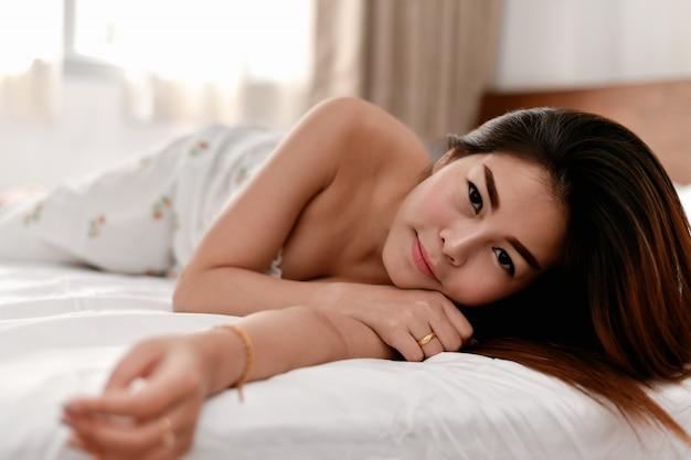 Het sexy meisje speelt in de slaapkamer.