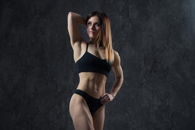 Het sexy meisje van sporten met grote spierbuik in een zwarte sportkleding op een zwarte achtergrond.