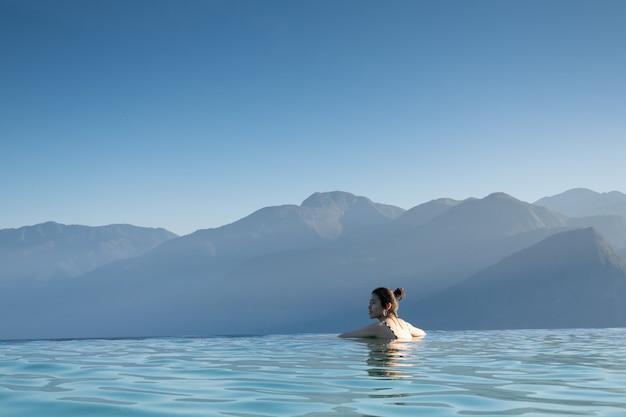 Het sexy vrouw ontspannen in oneindigheids zwembad die overweldigend bergmening bekijken bij luxueus toevlucht / vakantieconcept