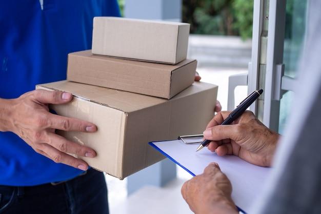 Het shoppermeisje tekent op het klembord om de pakketdoos van de bezorger te ontvangen. snelle bezorgservice