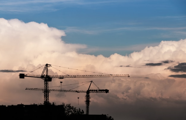 Het silhouet van bouwkranen tegen de hemel met grote wolken.