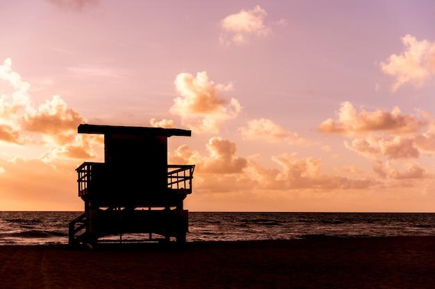 Het silhouet van de de patrouillehut van de het levenswacht in californië tijdens zonsondergang