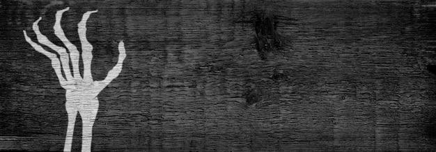 Het silhouet van de hand van een skelet. donkere houten achtergrond. het concept van de halloween-vakantie. ruimte kopiëren