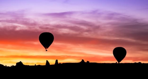 Het silhouet van de hete luchtballon in bergen bij zonsopgang
