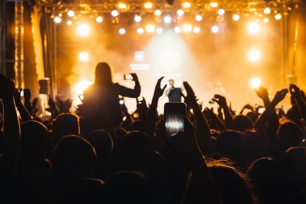 Het silhouet van de menigte van het publiek tijdens een concert van basta en een hand met een mobiele telefoon