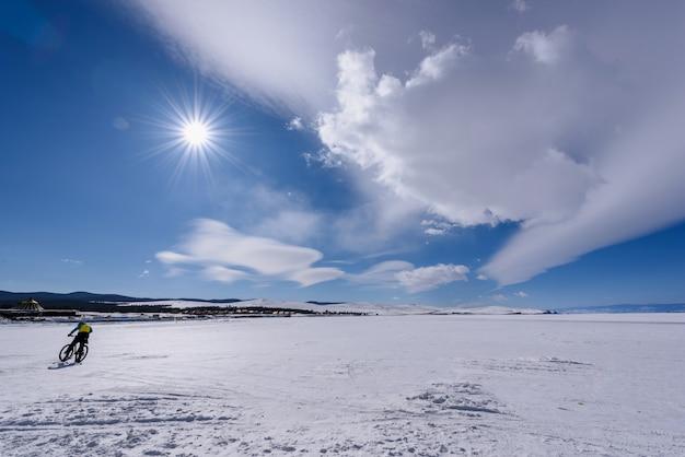 Het silhouet van de mens berijdt fiets op het bevroren meer baikal bij zonnig weer met mooie wolkenhemel