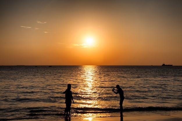 Het silhouet van de mensen neemt een foto op het strand.