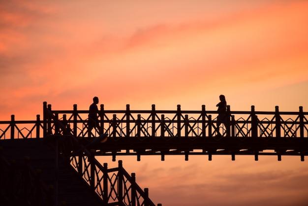 Het silhouet van de stalen brug en het licht na zonsondergang voor donker