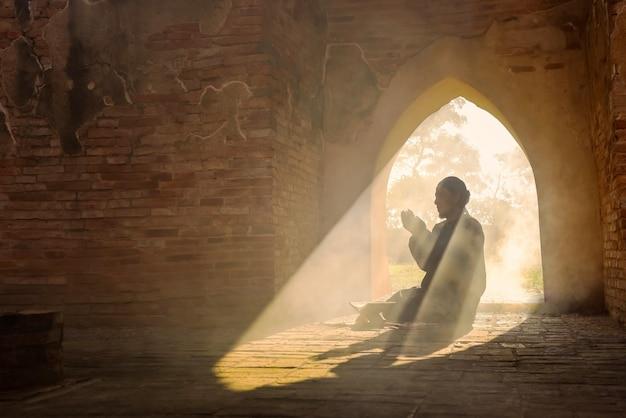 Het silhouet van een aziatische moslimman, die bidt in een kamer met zonlicht dat door de deur van de moskee schijnt