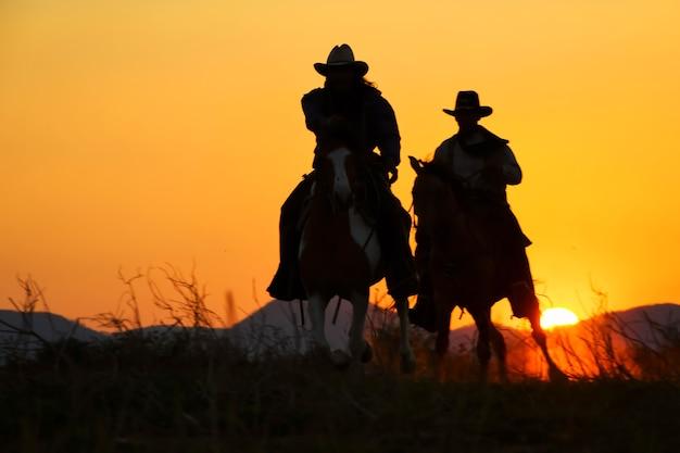 Het silhouet van een cowboy op een paard