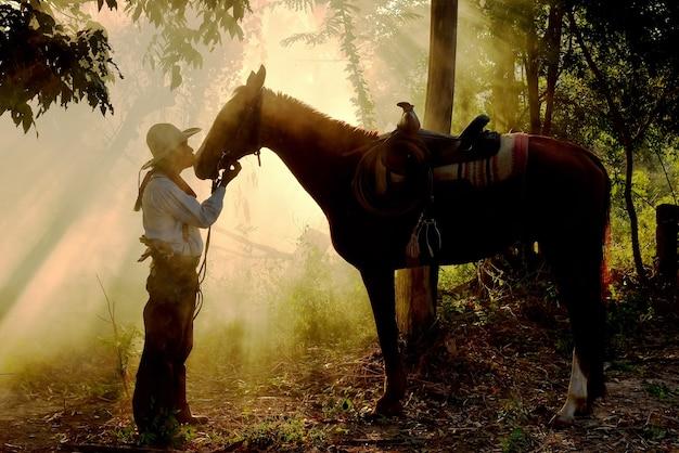 Het silhouet van een cowboyman met zijn paard en zonneschijn in de ochtend