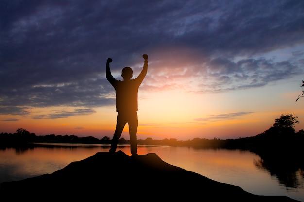 Het silhouet van een gelukkige man hief handen omhoog als een succesvolle, overwinning en bereikt een bedrijfsdoel in de zonsonderganghemel