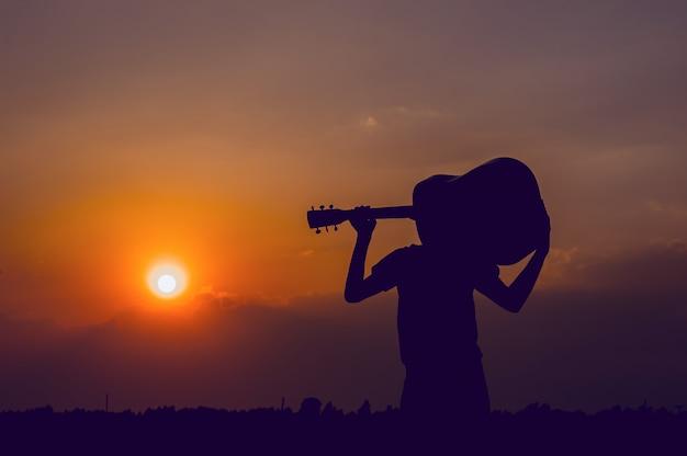 Het silhouet van een gitarist die een gitaar vasthoudt en een zonsondergang heeft, silhouetconcept.