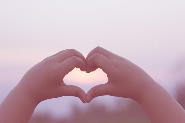 Het silhouet van een hand van kinderen in een prachtige zonsopgang vangt de zon in het hart.