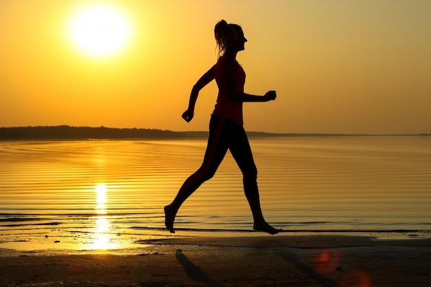 Het silhouet van een jong mooi meisje loopt langs de kust op de oranje zonsondergangachtergrond
