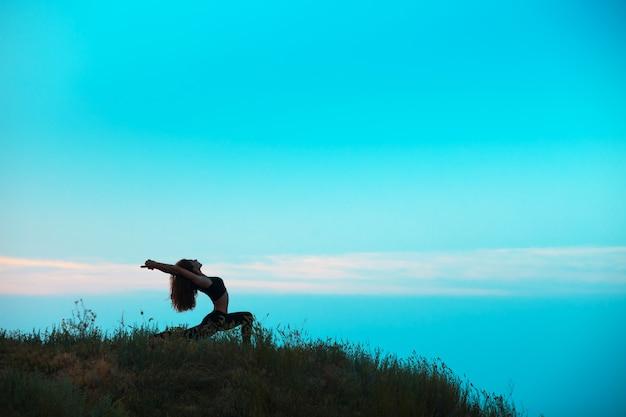 Het silhouet van een jonge vrouw beoefent yoga