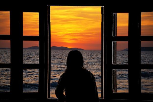 Het silhouet van een jonge vrouw kijkt door het raam met uitzicht op zee.