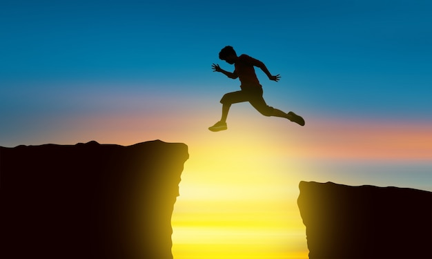 Het silhouet van een man die over de afgrond springt ten tijde van de zonsondergang, concept van overwinning en succes