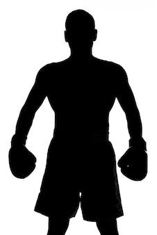 Het silhouet van een man met bokshandschoenen stelt.