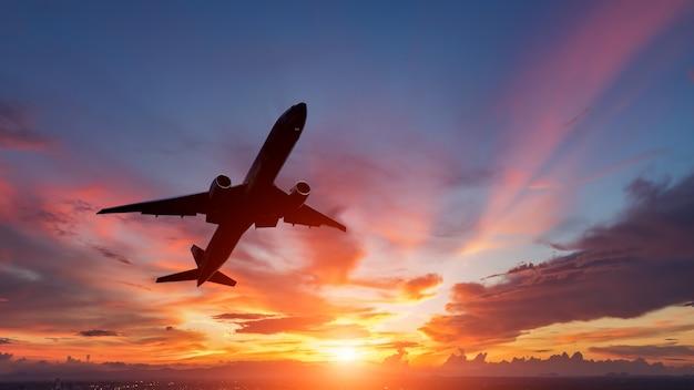 Het silhouet van een passagiersvliegtuig die in zonsondergang vliegen.