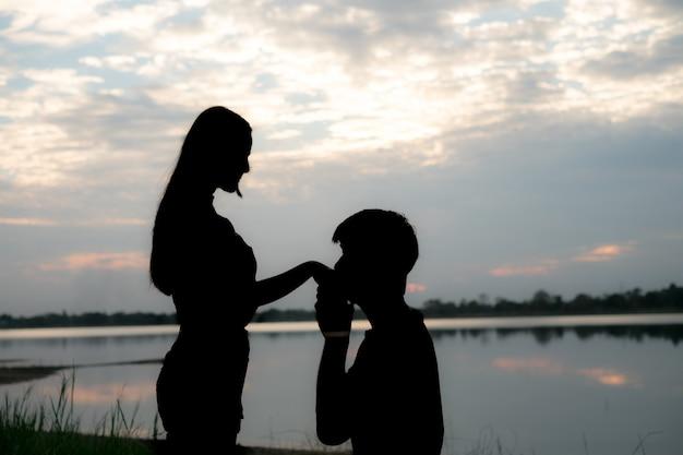 Het silhouet van een romantisch paar dat, elkaar koestert en de zonsondergang bekijkt bevindt zich. romantiek en liefde concept.
