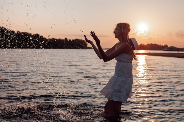 Het silhouet van een slanke vrouw bij zonsondergang een mooie jonge blonde in een zomerjurk en een stro h...