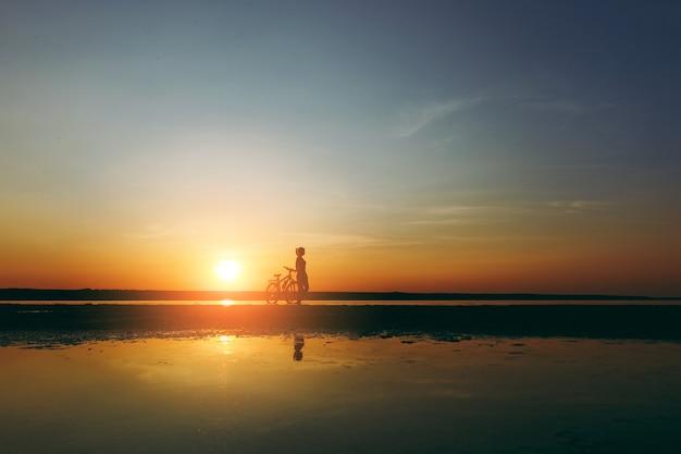 Het silhouet van een sportief meisje in een pak dat in de buurt van een fiets in het water staat bij zonsondergang op een warme zomerdag. geschiktheidsconcept.