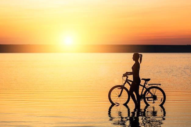 Het silhouet van een sportief meisje in een pak dat op een warme zomerdag op een fiets in het water zit bij zonsondergang. geschiktheidsconcept.