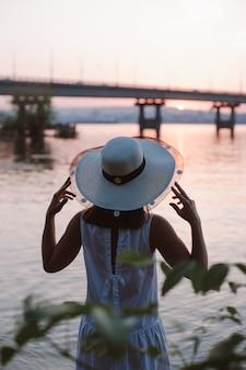 Het silhouet van een vrouw aan zee bij zonsondergang achteraanzicht van het silhouet van een jonge vrouw in een str...