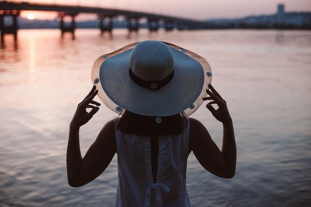 Het silhouet van een vrouw bij de rivier bij zonsondergang achteraanzicht van het silhouet van een vrouw in een stroh...