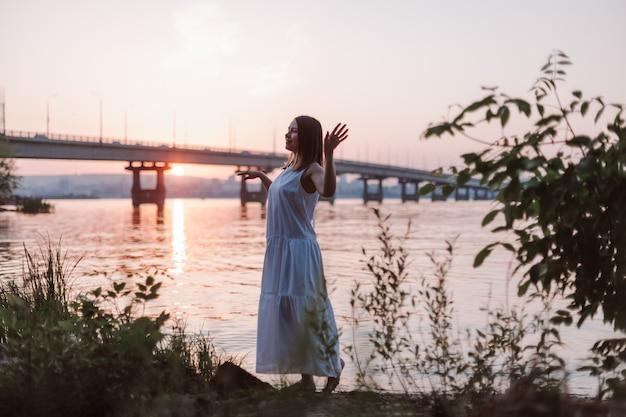 Het silhouet van een vrouw die danst bij zonsondergang levensstijl fulllength portret van een mooie vrouw geniet...